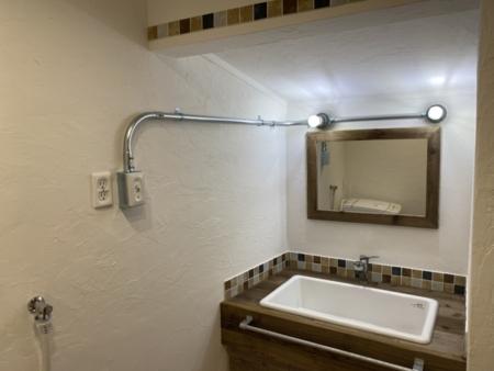 アクセントタイルと工業用照明の洗面台